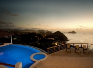 View from St Lucia\'s Best Holiday Villa Rental Entertainment level over the pool at Sunset towards Pigeon Island