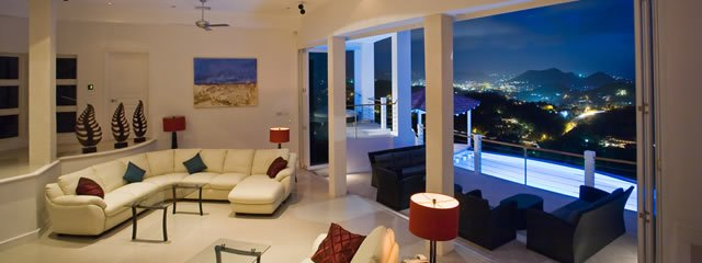 Akasha St Lucia's best Luxury Villa Rental. This is probably also The Caribbean Villa Rental. Stunning Living Room view as seen from the dining table at night looking out over the infinity pool and towards the lights of Rodney Bay